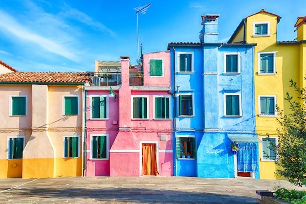 イタリア、ベニスの近くの曇りの青い空とブラーノ島のカラフルな家。