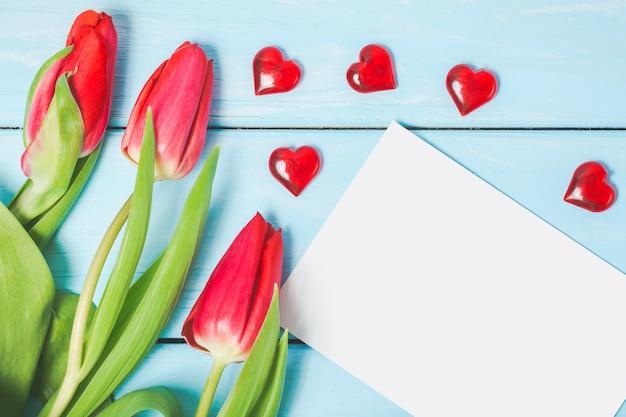 空白の写真と水色の木製の背景に装飾的な赤いハートのカラフルな春のチューリップの花。