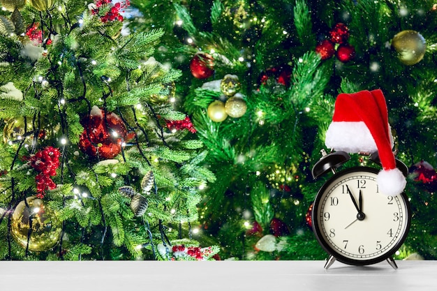 クリスマスツリーに対してサンタクロースの帽子とレトロな目覚まし時計