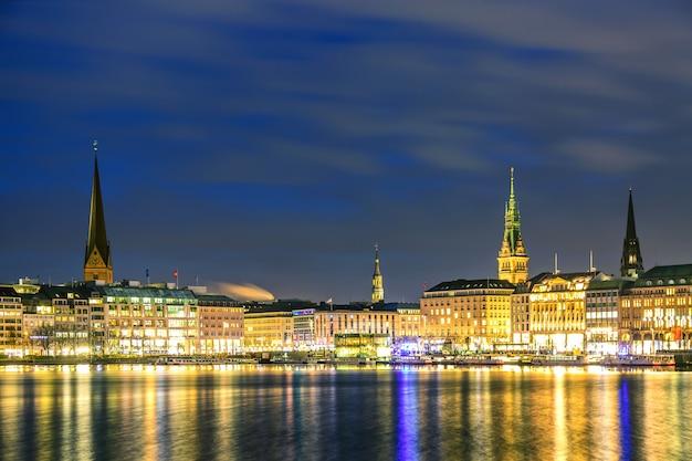 Озеро бинненальстер с освещенным центром города в гамбурге, германия во время сумеречного заката.