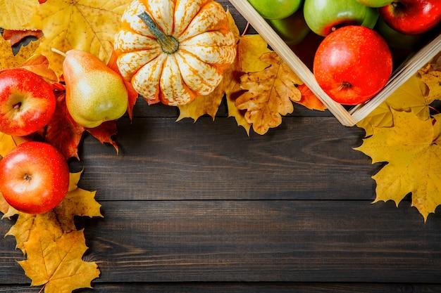 Спелые яблоки в коробке с тыквами, яблоками и грушами возле осенних листьев на фоне темных деревянных.