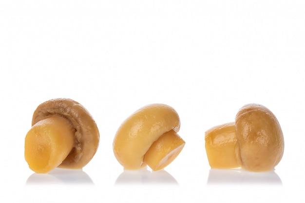 白い背景に分離されたおいしい漬けキノコのセットです。マリネシャンピニオングループ。