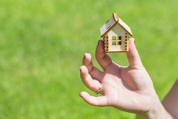 小さな木の家を持っている女性の手。