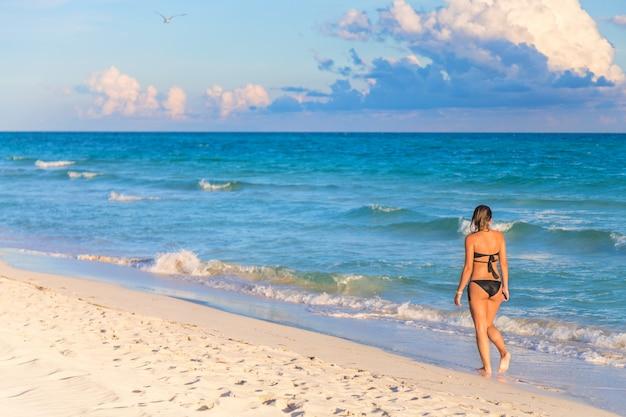 エキゾチックなビーチの上を歩くビキニの若い女性