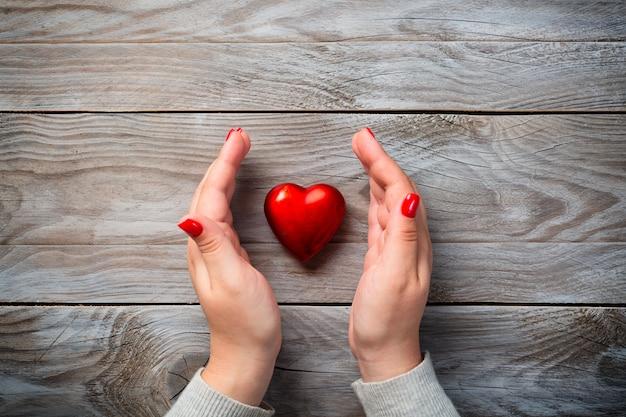 Женские руки с красными гвоздями и декоративным сердцем на деревянном фоне.