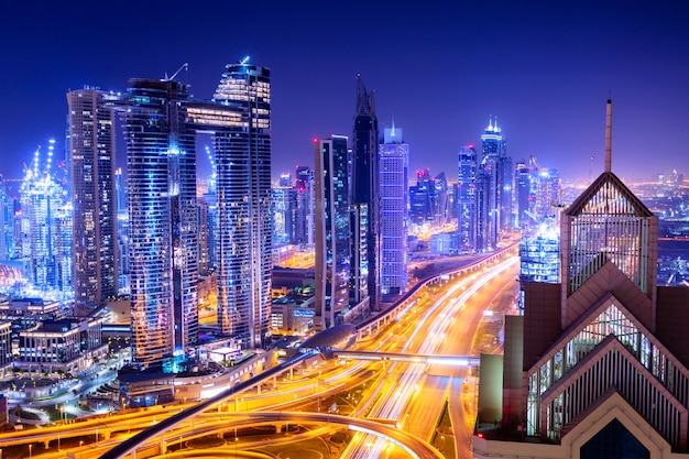 Удивительный горизонт городской пейзаж с подсветкой небоскребов. центр города дубай ночью, объединенные арабские эмираты.