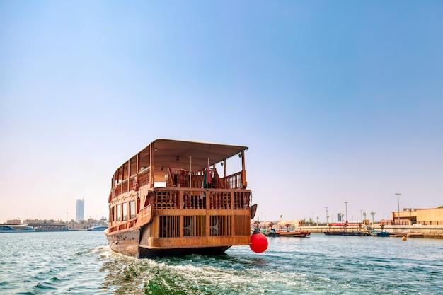 Туристический деревянный корабль в заливе дубай-крик в солнечный летний день. объединенные арабские эмираты.