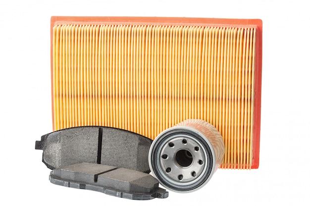 ブレーキパッド、オイルフィルター、エアフィルターのセット。白で隔離される車のスペア