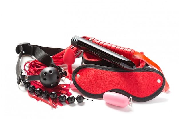 Кожаный кнут, батл, наручники, шарики, яйцо вибратор, фаллоимитатор, кляп и повязка на глазах, изолированные на белом