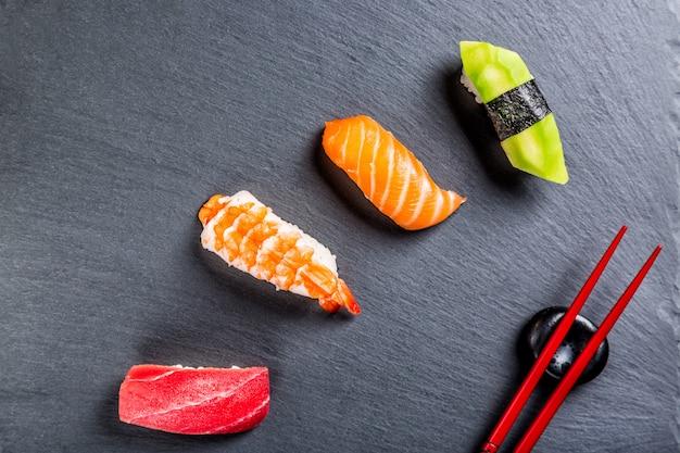 箸で黒いスレート板に様々な寿司。日本料理。