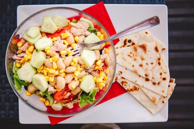 Вкусный рыбный салат с тунцом, салатом, фасолью, кукурузой, огурцом и помидорами в тарелке с вилкой,