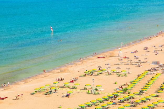 Аэрофотоснимок пляжа римини с людьми и голубой водой,