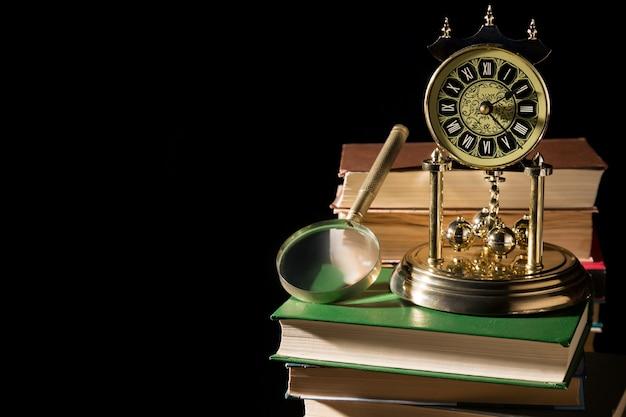 古い本のヴィンテージ時計の近くの虫眼鏡