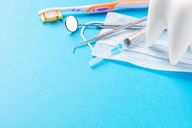 Инструменты стоматолога или инструменты стоматолога, зонд, стоматологическое зеркало, шприц, модель белого зуба, зубная щетка и маска для лица