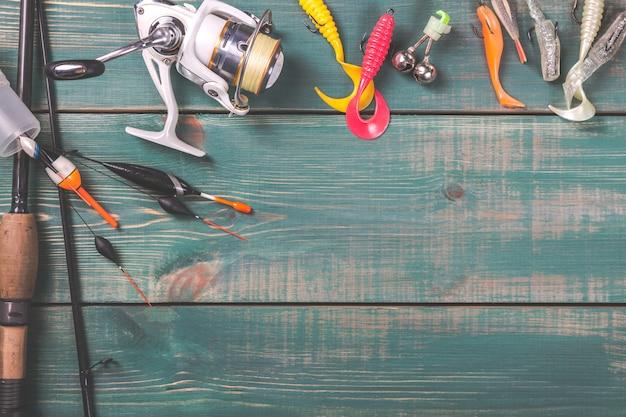Удочки, рыболовные снасти, катушки и рыболовные буи на зеленом фоне деревянных