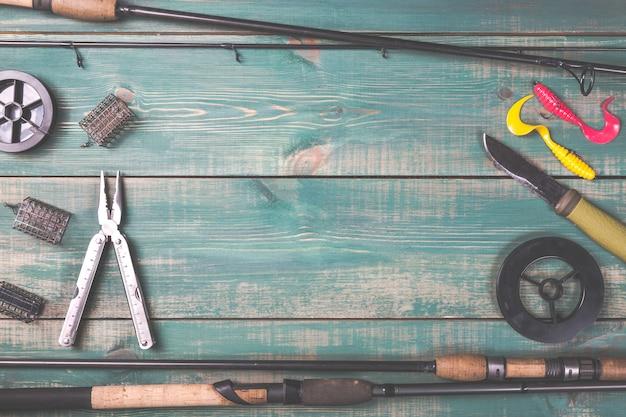 Удочки, рыболовные снасти, лески, нож и кормушки на зеленой деревянной