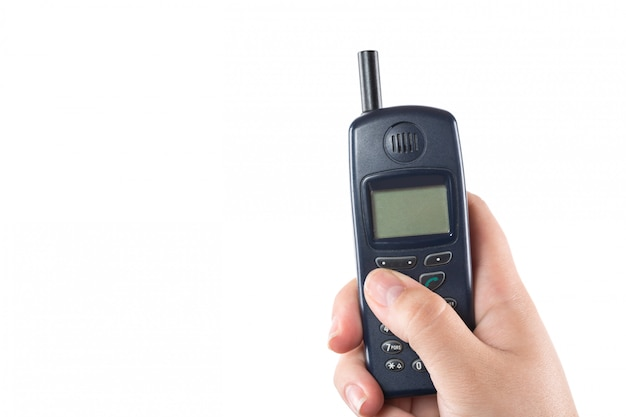 Рука женщины держа старый мобильный телефон изолированный на белизне