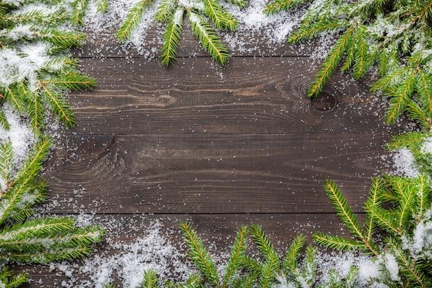 雪で暗い木の板にクリスマスのモミの木。