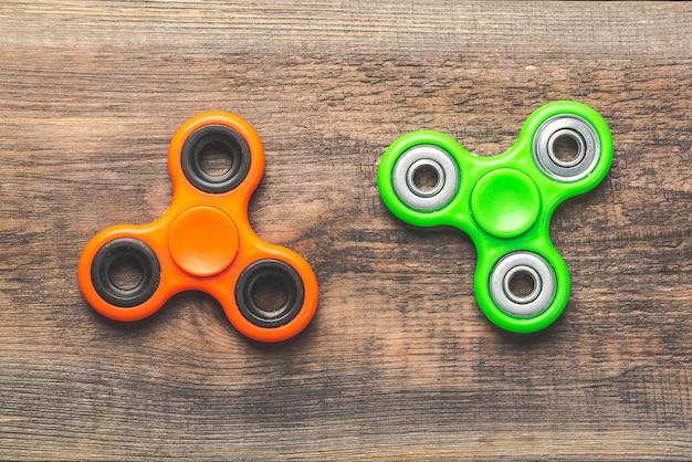 Оранжевые и зеленые непоседы закручивают близко друг к другу, снимающие напряжение игрушки на деревянной предпосылке