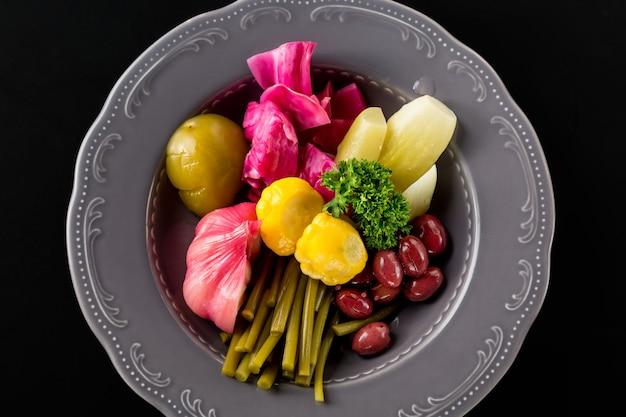 Маринованные овощи в железной пластине. чеснок, лук-порей, куст тыквы, зелень, огурец, капуста, фасоль.