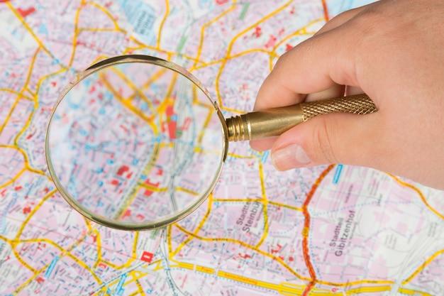 Женская рука держит увеличительное стекло над картой города