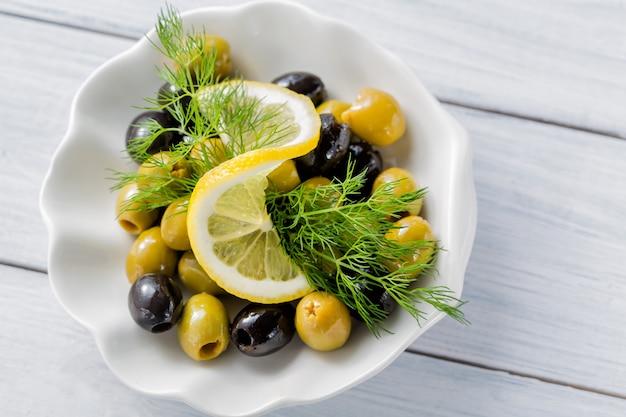 白い木製のテーブルにオリーブとディルとレモンのスライス