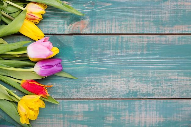 グリーティングカードとして緑の木製の背景にカラフルな春のチューリップの花