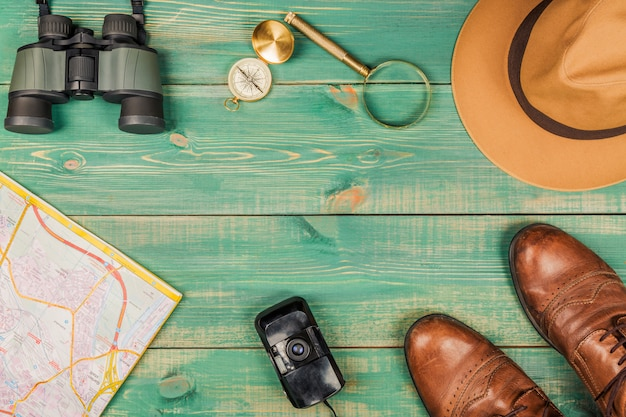 虫眼鏡、コンパス、市内地図、双眼鏡、茶色の靴、フェドラハット、古いフィルムカメラ