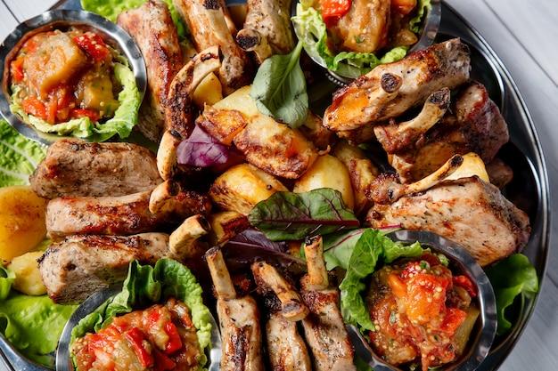 Мясная тарелка с вкусными кусочками мяса, салат, ребрышки, овощи на гриле, картофель и соус