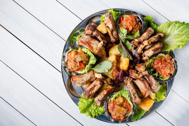 おいしい肉、サラダ、子羊のリブ、野菜のグリル、ポテト、ソースが入った肉プレート
