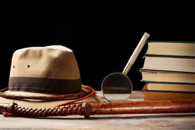 虫眼鏡と黒の古い本の近くの鞭とフェドーラ帽