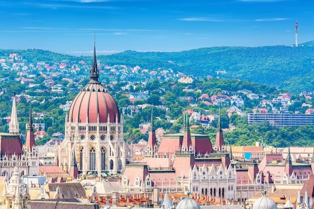 旅行とヨーロッパの観光コンセプト。青い空と雲と夏の晴れた日の間にハンガリーのブダペストの議会とブダ側のパノラマ。セントイストヴァンのバジルからの眺め。