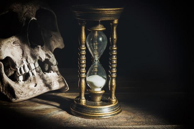 光のビームの下で木製の頭蓋骨とビンテージ砂時計