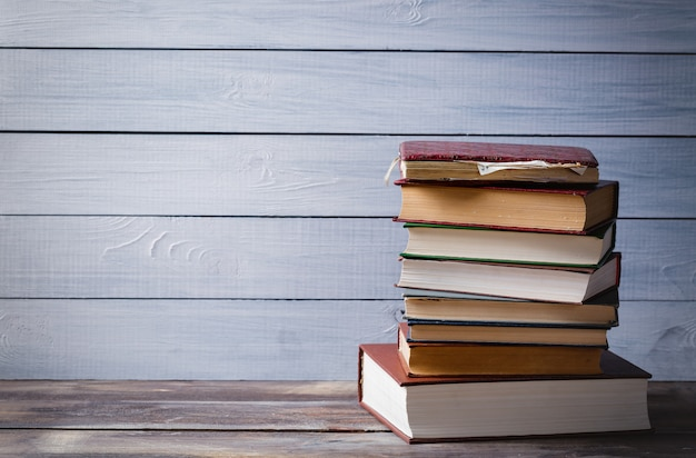 青い木製の背景上の古い本