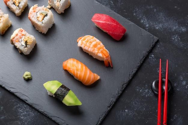 スレートプレートと箸とわさびと黒い石のテーブルにさまざまな寿司とロール