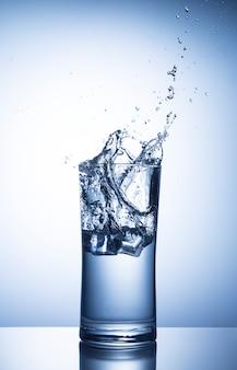 Кубики льда падают в стакан воды с всплеск
