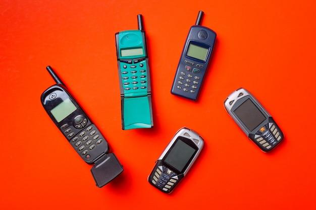 Старые старинные мобильные телефоны на красный апельсин