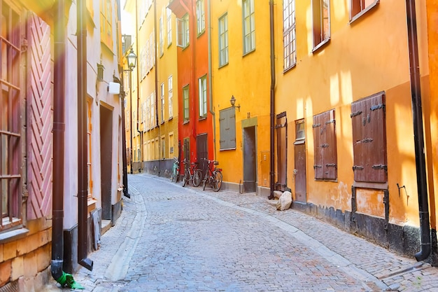 夏の晴れた日にストックホルムのガムラスタン歴史的旧市街の自転車と黄色い赤の中世の家々と狭い石畳の通り。