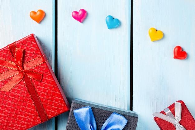 Красочные подарочные коробки с декоративными сердечками на приятном синем деревянном фоне
