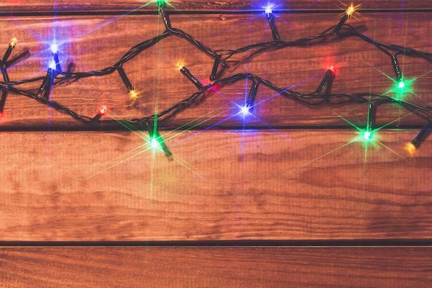 コピースペースを持つ木製の背景にバレンタインやクリスマスのロマンチックなライト