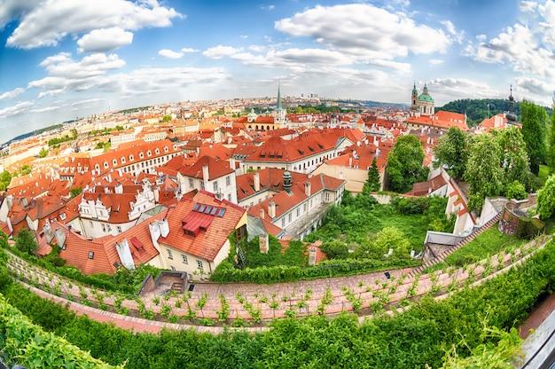 チェコ共和国のプラハマラーストラナ地区の伝統的な赤い屋根と木々のある家、魚眼レンズ