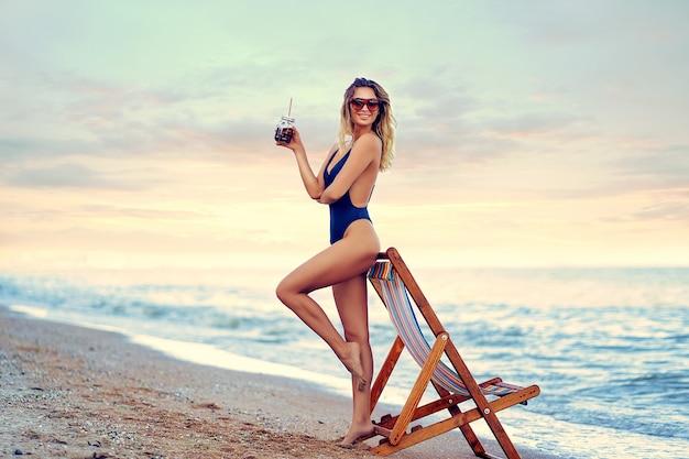 サングラス、ビーチでリラックスした水着とカクテルの素晴らしい美しさ金髪女性