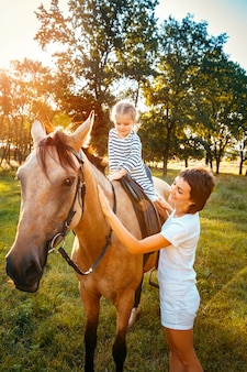 近くに立っている母親と馬に乗って小さな女の子