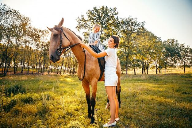 Маленькая девочка верхом на лошади с ее матерью стоя рядом