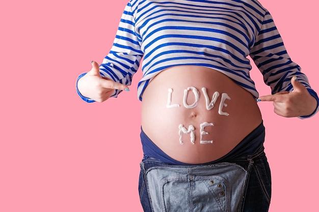 Беременная женщина пишет слово «люби меня» на животе.