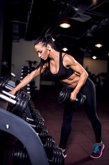 Фитнес девушка подъема гантелей