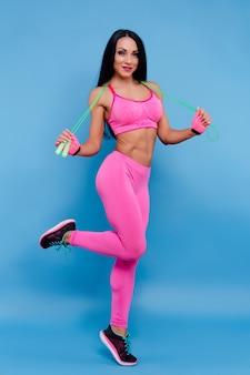 縄跳びとピンクのスポーツウェアで陽気なブルネットの少女