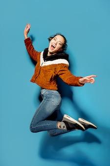 青い背景上の空気中のカジュアルなジャンプの若い女性