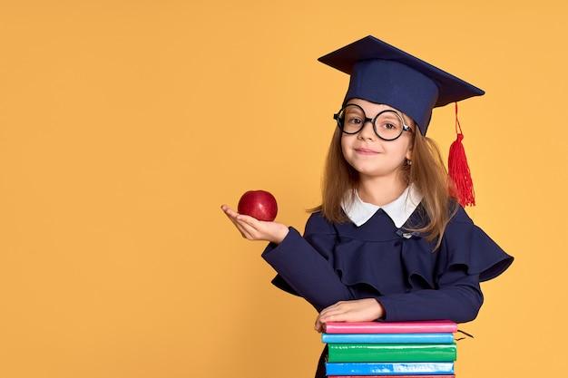 Веселая школьница в выпускной наряд, несущий яблоко, стоя рядом с кучей учебников
