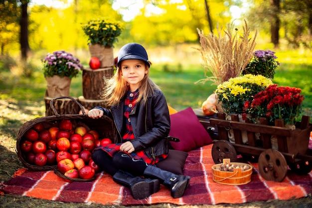 Улыбающийся ребенок с корзиной красных яблок, сидя в осеннем парке
